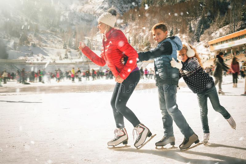 Happy family outdoor ice skating at rink. Winter activities. Happy family outdoor ice skating at rink. Mother and children has winter activities. Mom, kids stock photos
