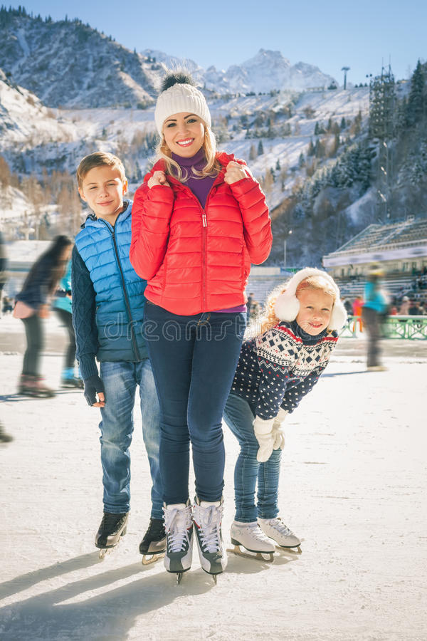 Happy family outdoor ice skating at rink. Winter activities. Happy family outdoor ice skating at rink. Mother and children has winter activities. Mom, kids royalty free stock image