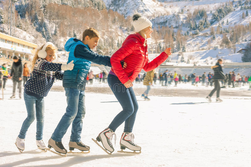Happy family outdoor ice skating at rink. Winter activities. Happy family outdoor ice skating at rink. Mother and children has winter activities. Mom, kids royalty free stock images