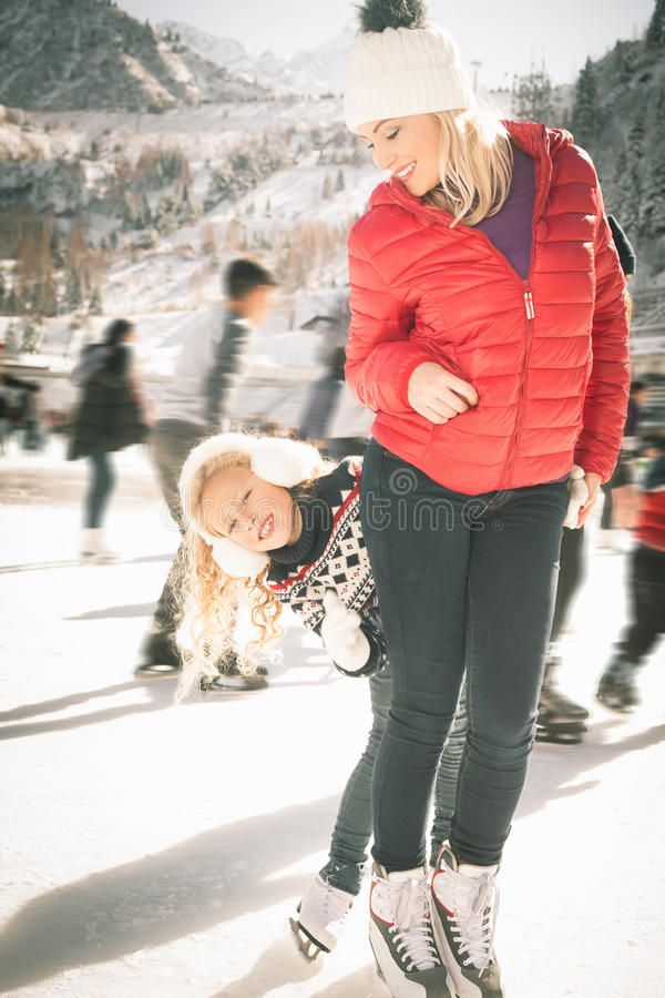 Happy family outdoor ice skating at rink. Winter activities. Happy family outdoor ice skating at rink. Mother and daughter has winter activities. Mom, kids stock images