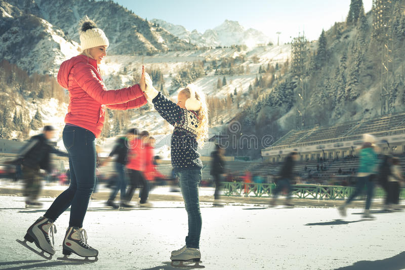 Happy family outdoor ice skating at rink. Winter activities. Happy family outdoor ice skating at rink. Mother and daughter has winter activities. Mom, kids stock image