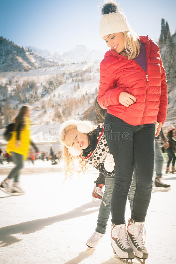 Happy family outdoor ice skating at rink. Winter activities. Happy family outdoor ice skating at rink. Mother and daughter has winter activities. Mom, kids stock photo
