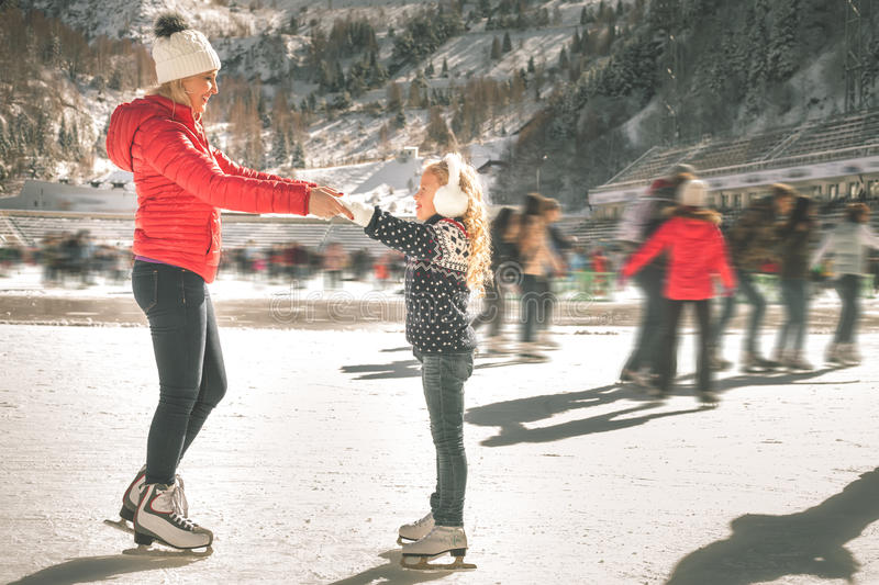 Happy family outdoor ice skating at rink. Winter activities. Happy family outdoor ice skating at rink. Mother and daughter has winter activities. Mom, kids stock photos