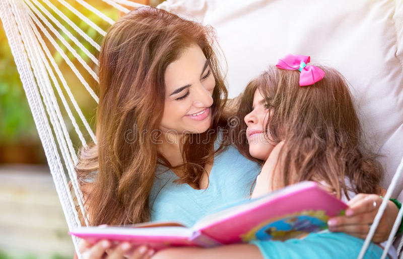 Happy family outdoors. Happy beautiful mother with cute little daughter sitting on backyard in hammock and reading interesting book, family spending time stock photos