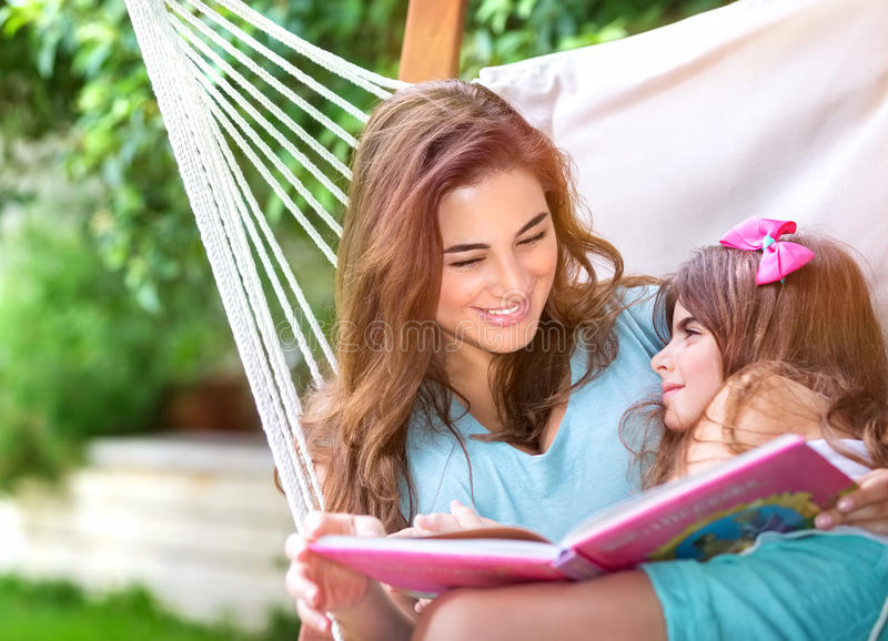 Happy family outdoors. Happy beautiful mother with cute little daughter sitting on backyard in hammock and reading interesting book, family spending time royalty free stock images