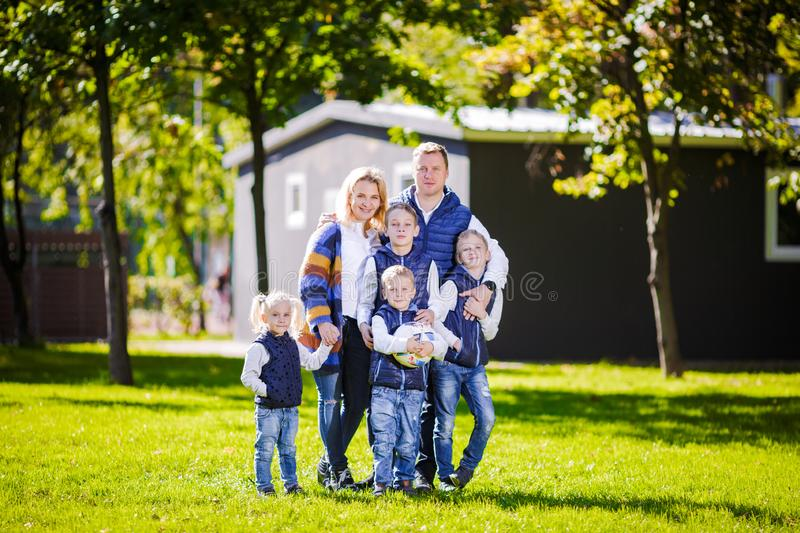 Happy Family Outdoors. Happy Caucasian family standing outside their house and hugging. Family with four children in front house. stock image