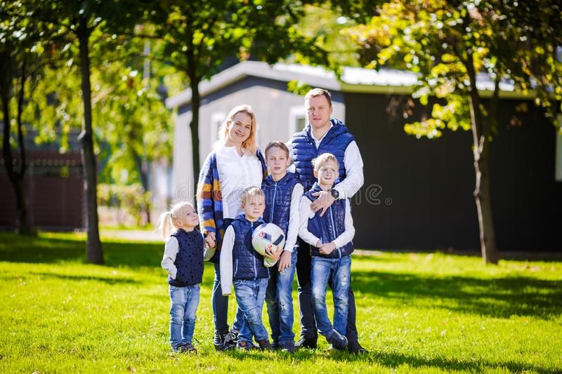 Happy Family Outdoors. Happy Caucasian family standing outside their house and hugging. Family with four children in front house. stock photo