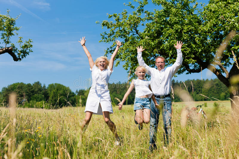 Happy family outdoors jumping royalty free stock photography