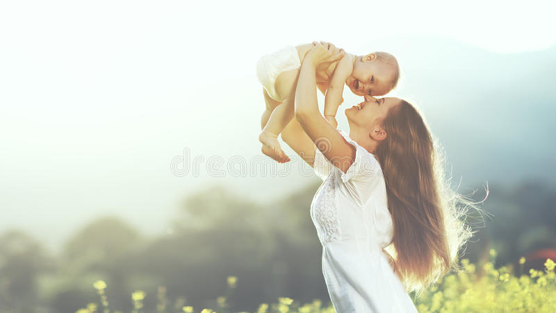Happy family outdoors. mother throws baby up, laughing and playing in summer on nature. Happy harmonious family outdoors. mother throws baby up, laughing and royalty free stock image