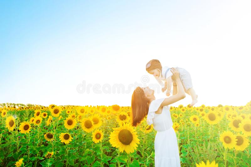 Happy family outdoors. Mother throws baby up, laughing and playing in the sunflowers field in summer on the nature royalty free stock images