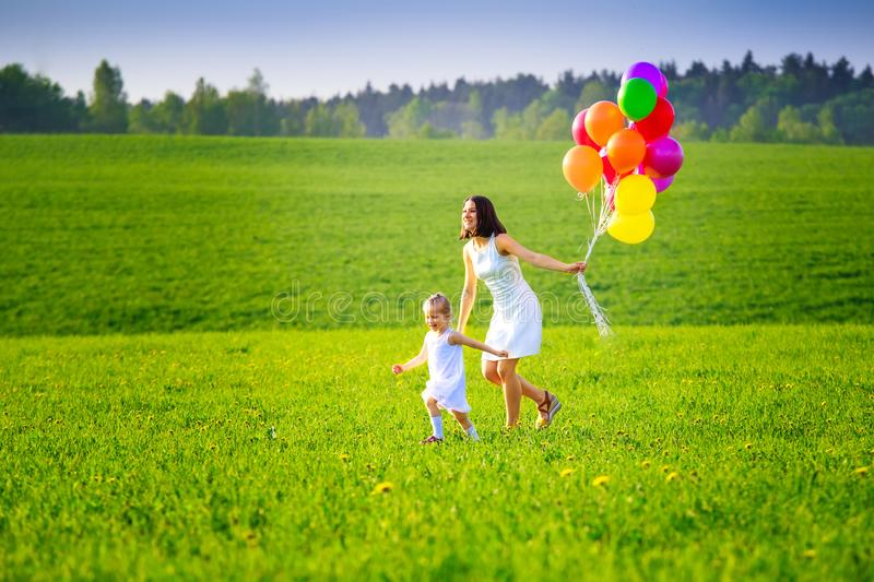 Happy family outside in summer evening. Mom and daughter running on green meadow with colorful balloons. Summer background stock photos