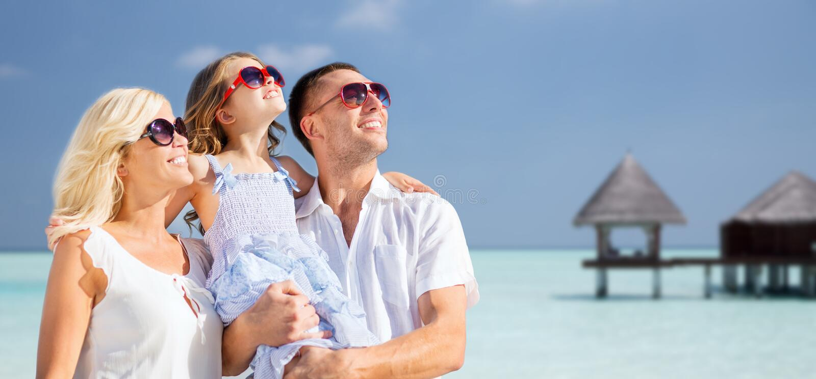 Happy family over tropical beach with bungalow. Summer holidays, travel, tourism, vacation and people concept - happy family over exotic tropical beach with stock photo