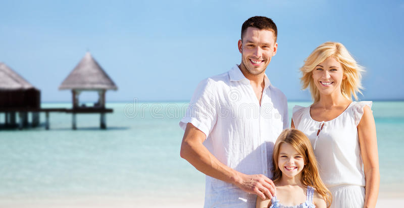 Happy family over tropical beach with bungalow. Summer holidays, travel, tourism, vacation and people concept - happy family over exotic tropical beach with royalty free stock photos