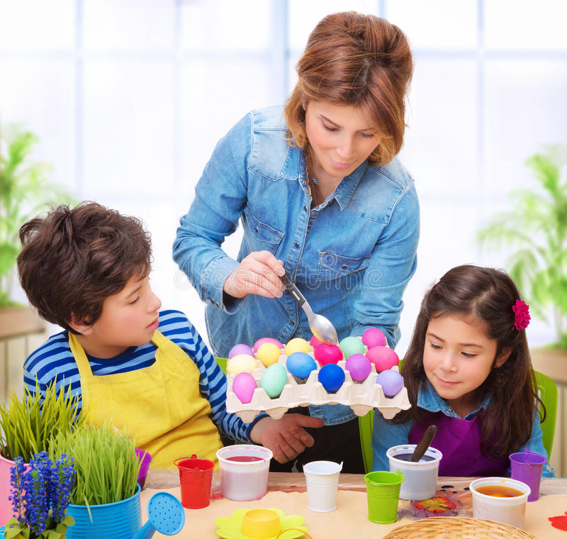 Happy family paint Easter eggs stock photography