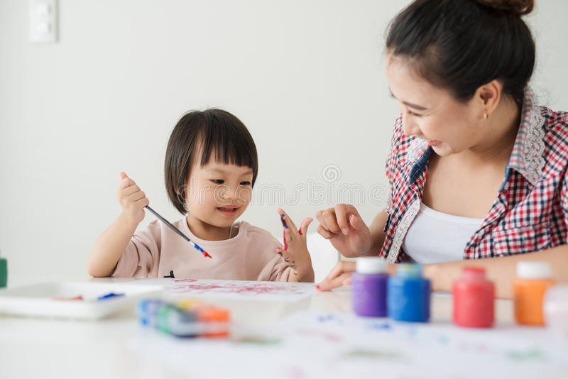 A happy family is painting. Mom help her daughter drawing.  royalty free stock image