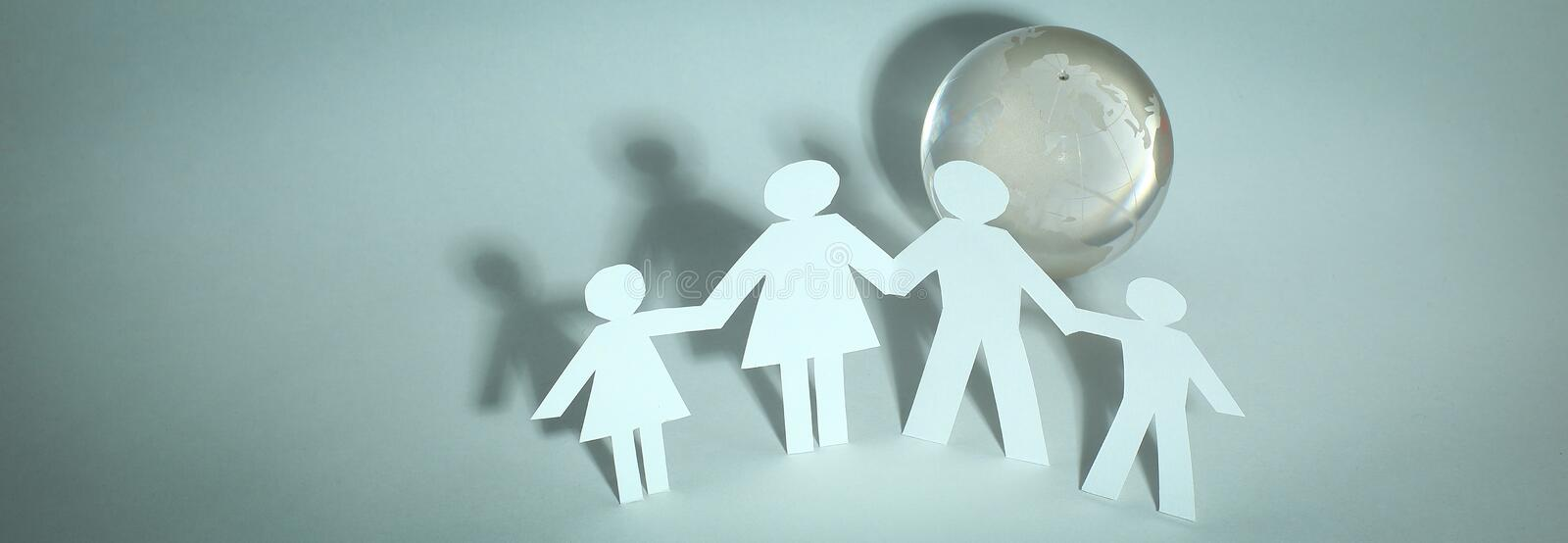 Happy family of paper men standing near the glass globe stock image