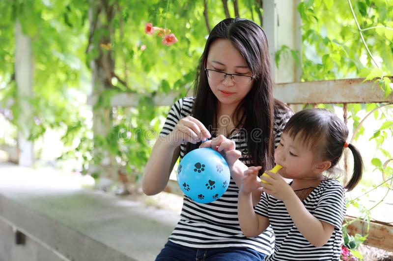 Happy family parental child time mother love children daughter play with baby girl blew balloon together have fun in summer park. A little Asian Chinese girl royalty free stock photography