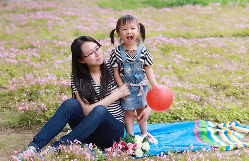 Happy family parental child time mother love children daughter play with baby girl blew balloon together have fun in summer park. A little Asian Chinese girl royalty free stock images