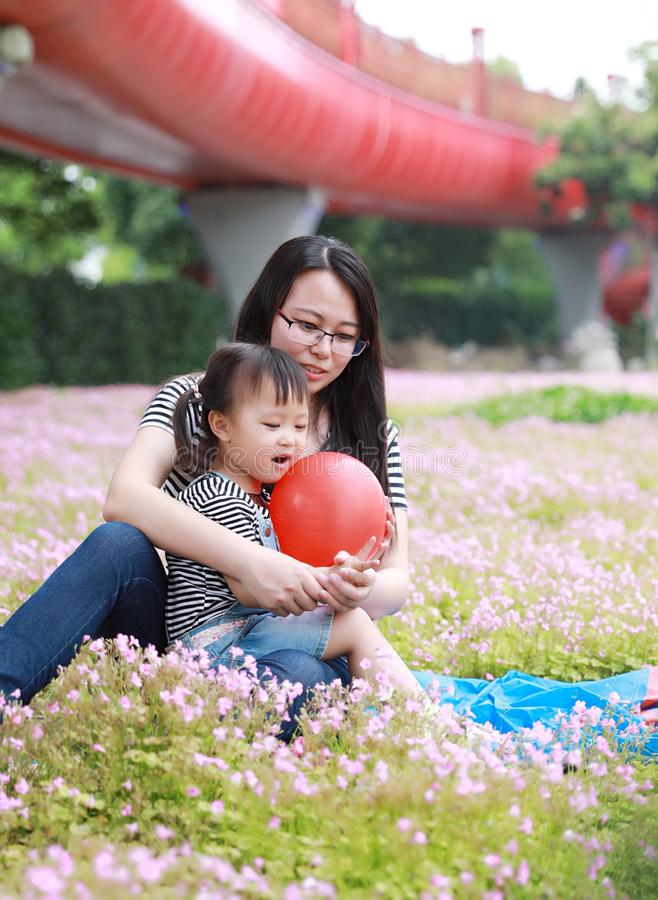 Happy family parental child time mother love children daughter play with baby girl blew balloon together have fun in summer park. A little Asian Chinese girl stock photos