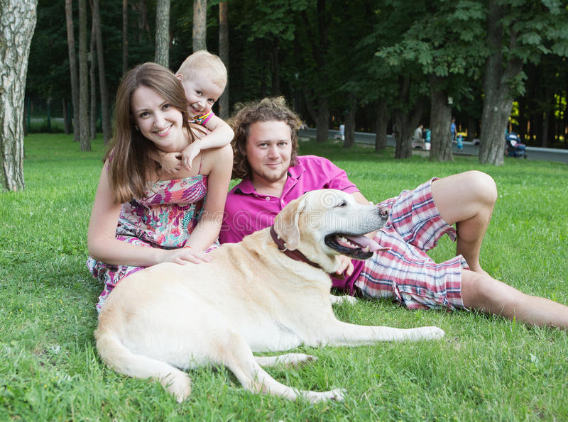 Happy family in the park. Happy young family with dog is resting in the park royalty free stock photo