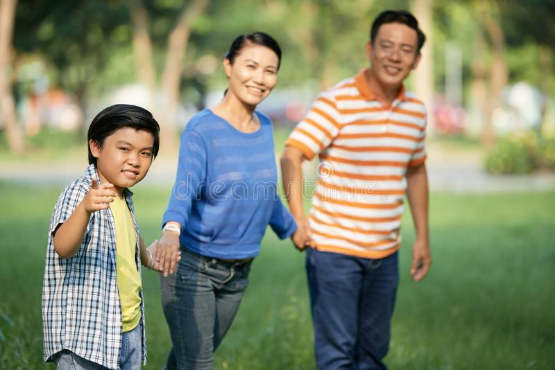 Happy family in park. Cheerful teenage men holding hand of his parents and pointing at camera stock image