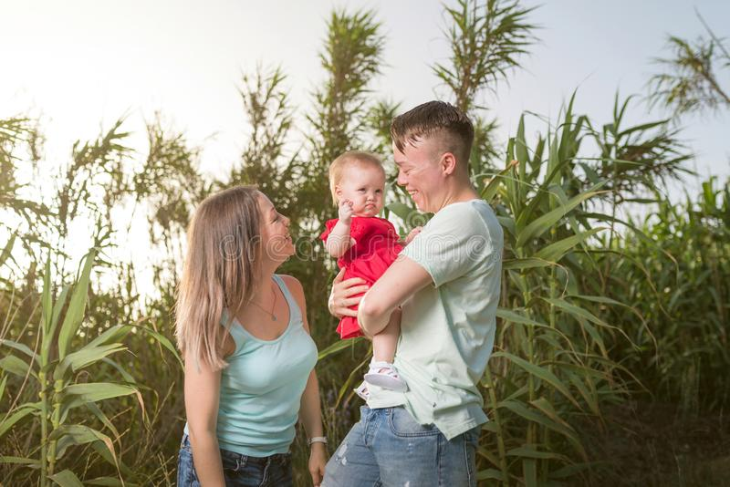 Happy family in the park evening light. The lights of a sun. Mom, dad and baby happy walk at sunset. The concept of a happy family royalty free stock photography