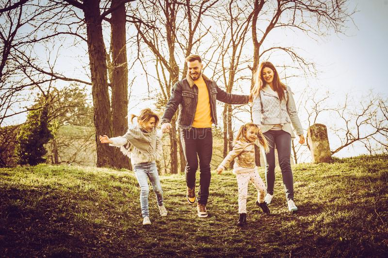 Happy family in the park. Happy family run through the park. On the move royalty free stock photography