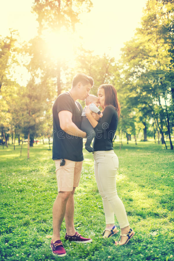 Happy family in park, mother and father holding and kissing a few months old son, kid. Infant portrait and happy family concept royalty free stock photos