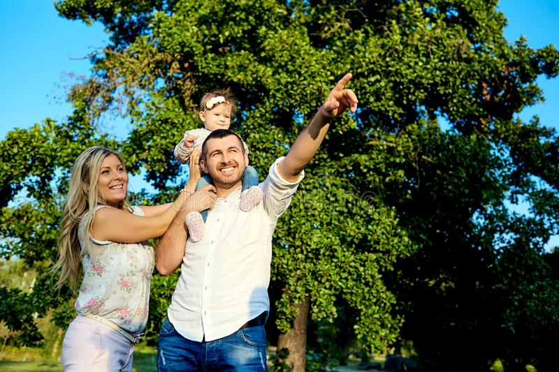 Happy family in a park in summer autumn. Mother, father and baby play in nature in the rays of sunset stock photos