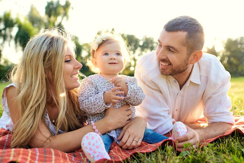Happy family in a park in summer autumn. Mother, father and baby play in nature in the rays of sunset stock photo