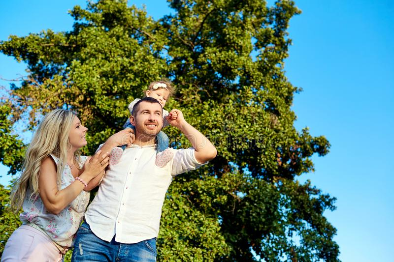 Happy family in a park in summer autumn. Mother, father and baby play in nature in the rays of sunset stock photography