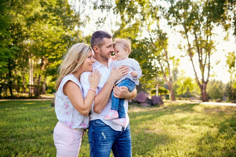 Happy family in a park in summer autumn. Mother, father and baby play in nature in the rays of sunset royalty free stock photo