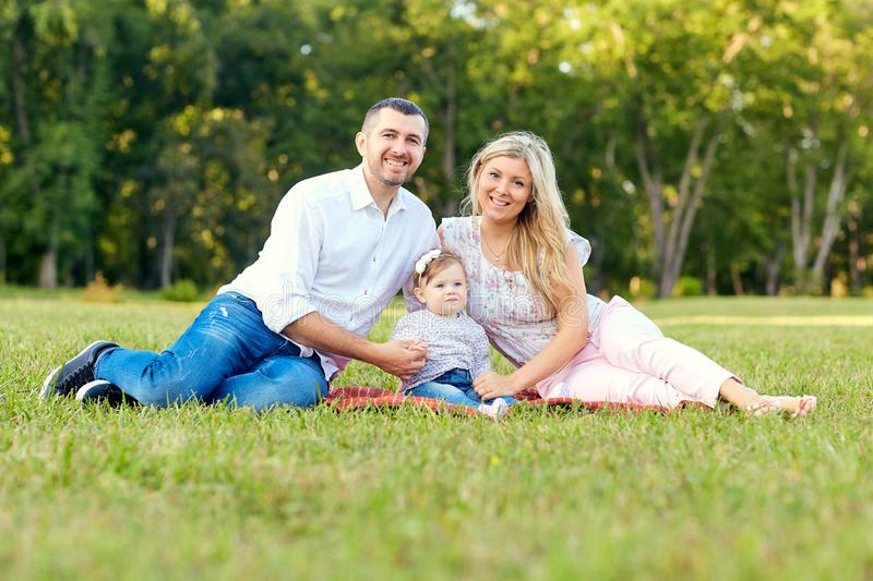 Happy family in a park in summer autumn. Mother, father and baby. Play in nature in the rays of sunset royalty free stock images