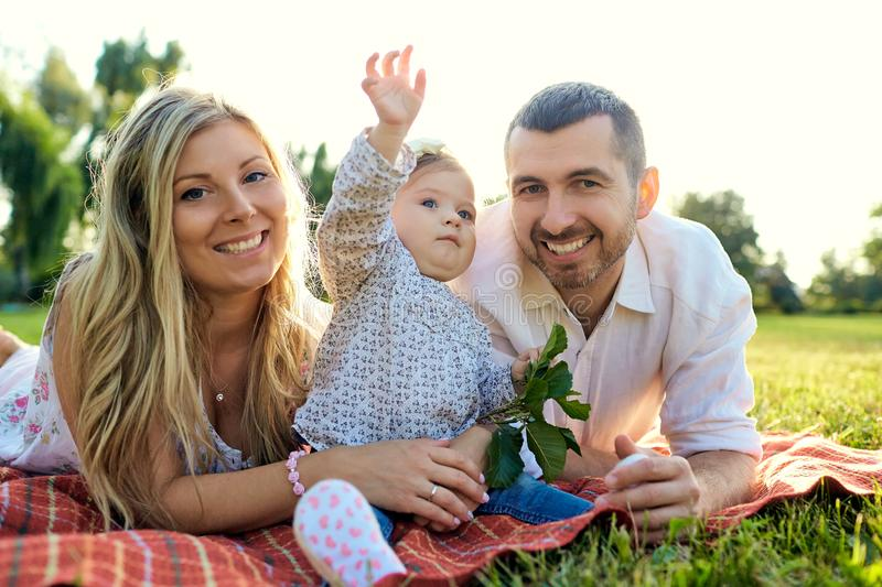 Happy family in a park in summer. Happy family in a park in summer autumn. Mother, father and baby play in nature in the rays of sunset royalty free stock photography