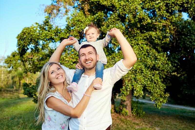 Happy family in a park in summer autumn. Mother, father and baby play in nature in the rays of sunset royalty free stock images