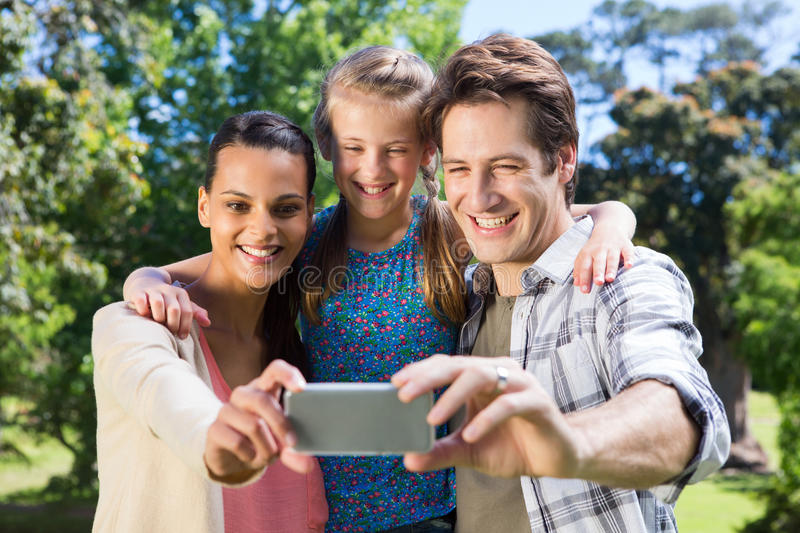 Happy family in the park taking selfie royalty free stock image