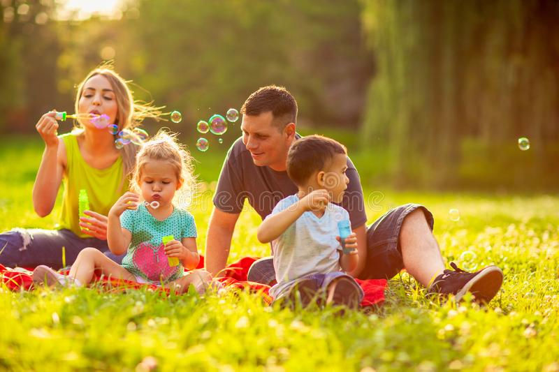 Happy family in the park- family with children blow soap bubbles. Happy family in the park- Young family with children blow soap bubbles outdoor royalty free stock image