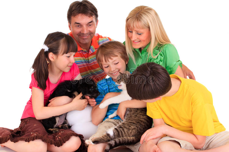 Happy family with pets. Happy family shown playing with their pet dog and cat. Isolated against a white background royalty free stock image
