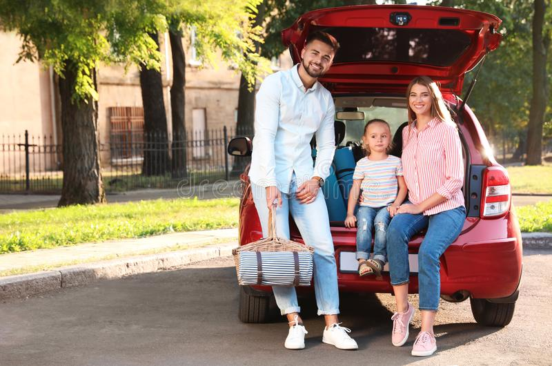 Happy family with picnic basket sitting in car`s trunk royalty free stock photography