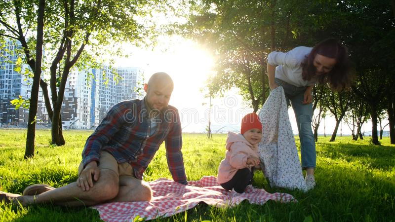 Happy family on a picnic with a child resting on nature at sunset in the park. Happy family on a picnic with a child resting on nature at sunset in the park stock images
