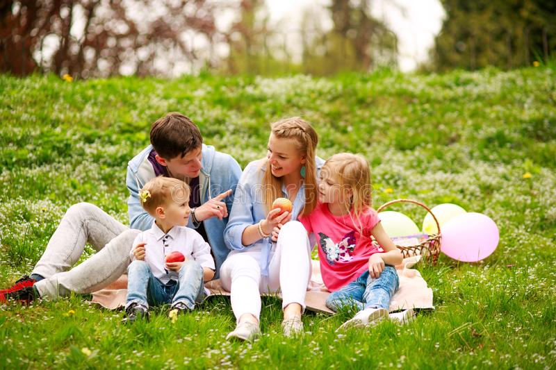 Happy family on picnic in flowered park sitting on grass, parenthood leisure in nature. Happy family on a picnic in the flowered park sitting on the grass royalty free stock image