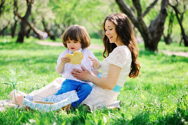 Happy family on picnic for mothers day. Mom and toddler son eating sweets outdoor in spring or summer royalty free stock image