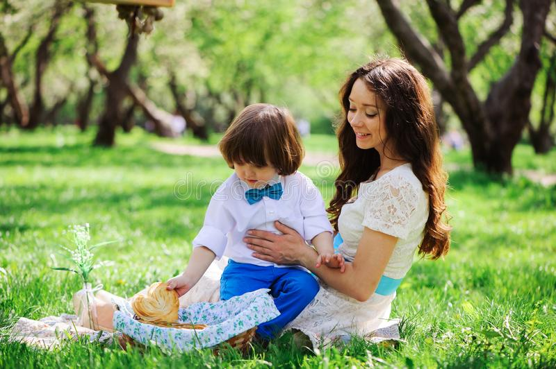 Happy family on picnic for mothers day. Mom and toddler son eating sweets outdoor in spring or summer stock photo