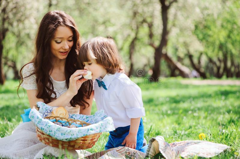Happy family on picnic for mothers day. Mom and toddler son eating sweets outdoor in spring stock photos