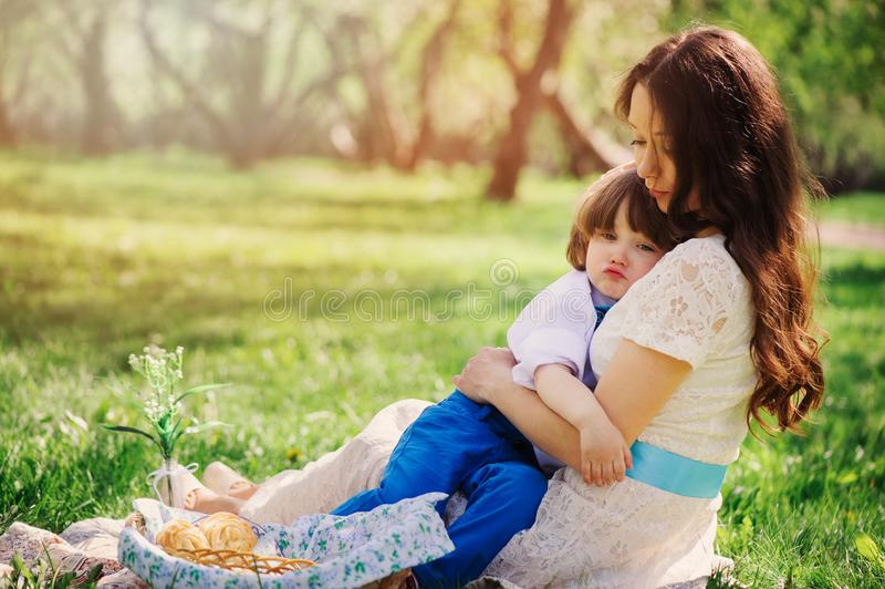 Happy family on picnic for mothers day. Mom and toddler son eating sweets outdoor in spring or summer stock images