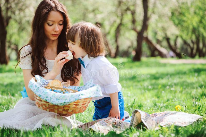 Happy family on picnic for mothers day. Mom and toddler son eating sweets outdoor in spring royalty free stock photography