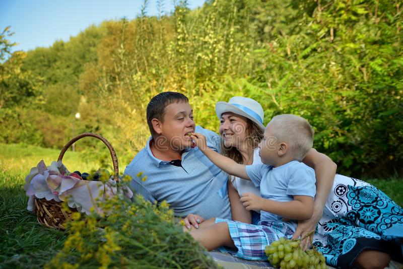 Happy family picnic in the park on summer day. Mom, dad and a little boy. The boy feeds the Pope grapes and laughing. Along with them. Family picnic in nature royalty free stock image