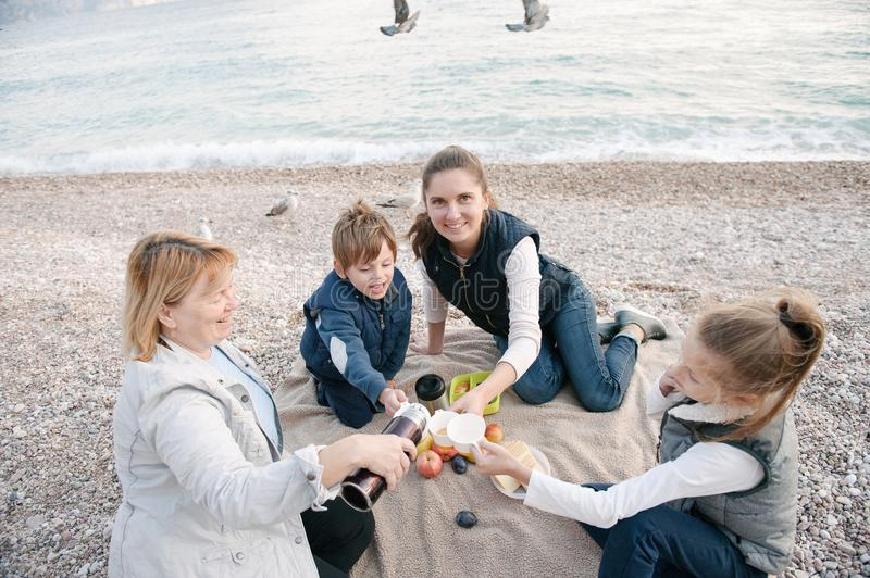 Happy family on picnic by the sea coast in overcast weather royalty free stock photography