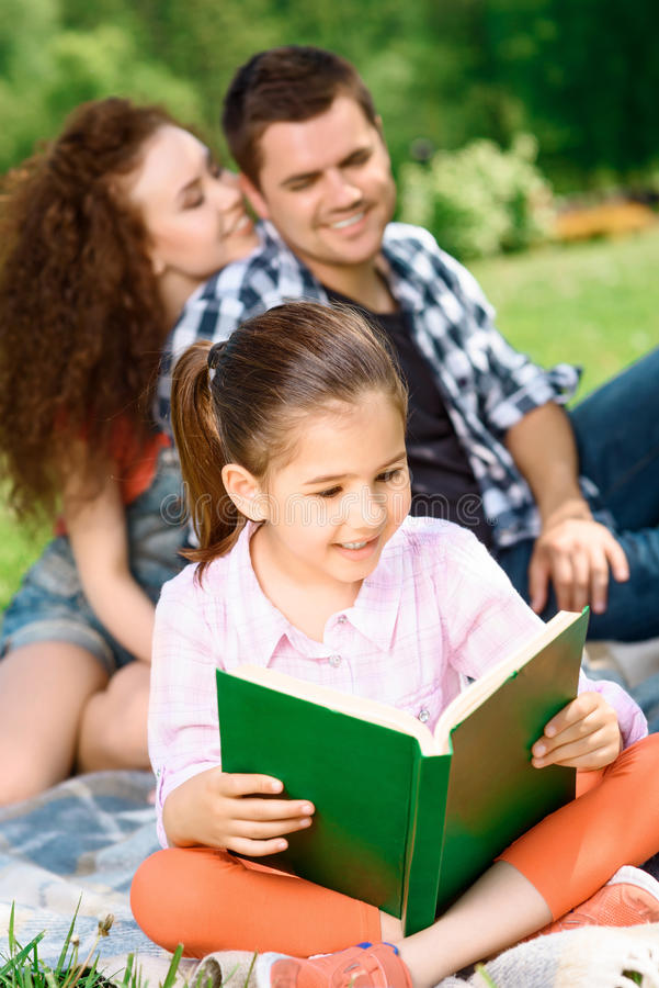 Happy family on a picnic. Small pretty girl sitting on a plaid on a green grass reading a book and her mother and father hugging on a background, enjoying family stock image