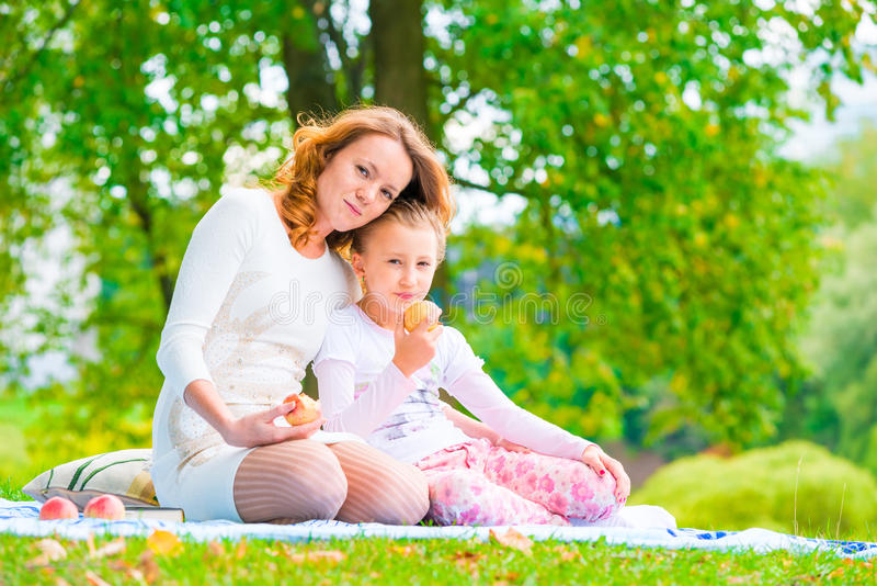 Happy family on a picnic snack apples. In the park stock image